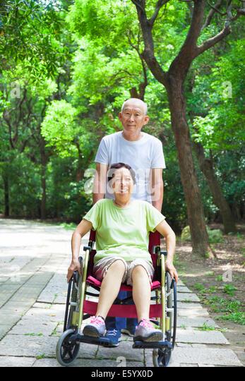 ältere Frau saß auf einen Rollstuhl mit seinem Mann Stockbild
