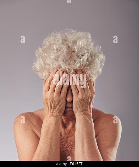 Porträt einer Frau mit dem Kopf in die Hände vor grauem Hintergrund verärgert. Traurige senior Frau Stockbild