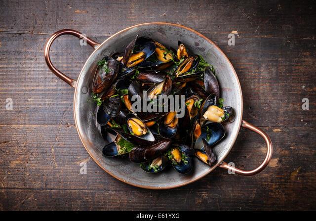 Gekochte Muscheln in Kupfer Kochen Gericht auf dunklem Holz Stockbild