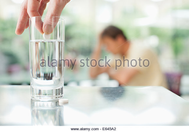 Pille aufstellen in Glas Wasser, mit unglücklichen Mann im Hintergrund Stockbild