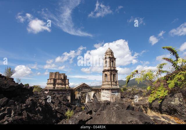 Die Türme des Tempels sind alle, die des Dorfes von Lava aus dem Vulkan Paricutín, Michoacan, Mexiko abgedeckt Stockbild