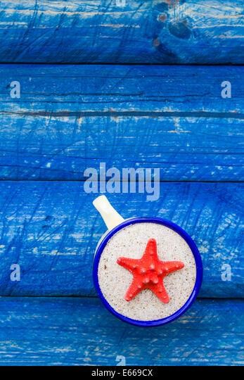 Jakobsmuschel-Farbe in der Tasse auf blauer Tisch Stockbild