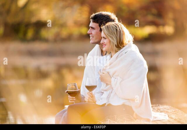 romantische junges Paar mit Rotwein im Freien am herbstlichen See Stockbild