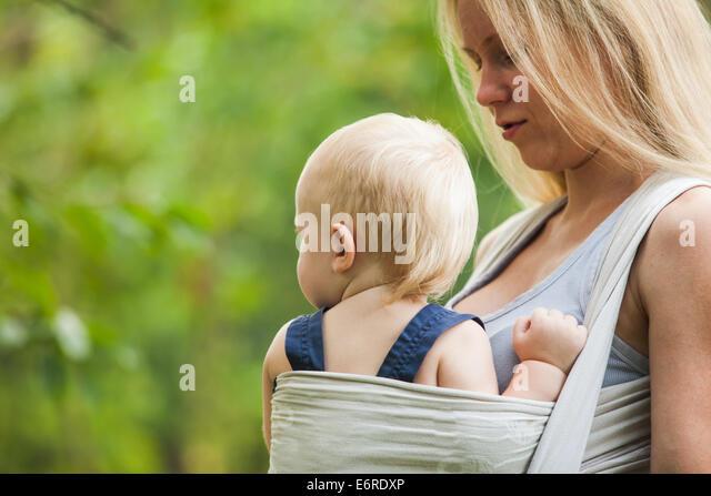 Mutter ist ihr Kind tragen und Fuß. Baby im Tragetuch im Freien. Stockbild