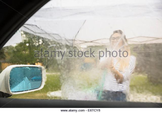 Frau Spritzen Autofenster mit Schlauch Stockbild