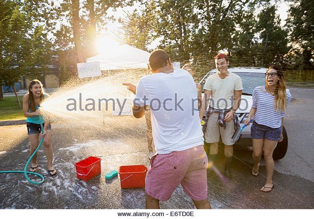 Frau Mann mit Schlauch in Autowaschanlage Spritzen Stockbild