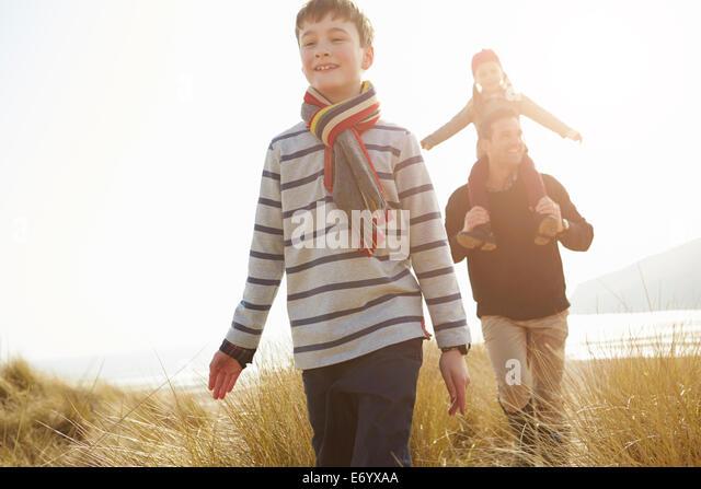 Vater und Kinder zu Fuß durch die Dünen am Strand von Winter Stockbild