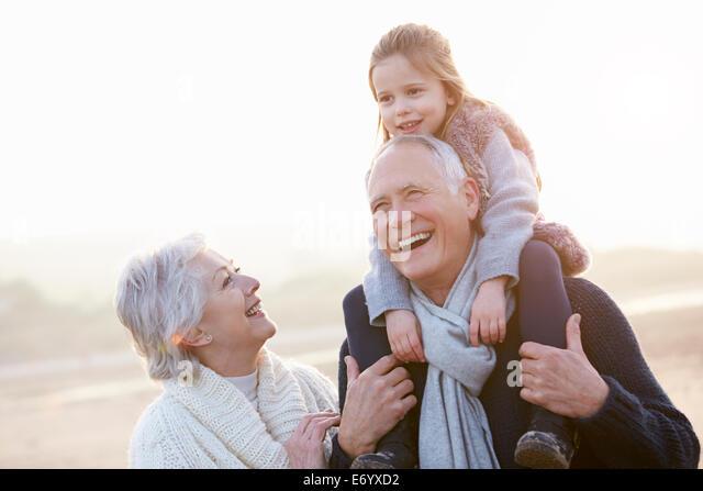 Großeltern und Enkeltochter zu Fuß am Strand von Winter Stockbild