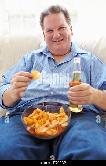 Übergewichtiger Mann zu Hause essen Chips und Bier zu trinken Stockbild