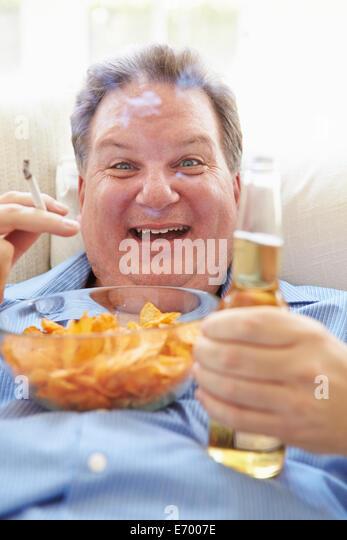 Übergewichtige Menschen essen Chips, Bier trinken und Rauchen Stockbild
