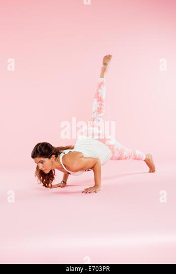 Studioaufnahme der jungen Frau in Yogaposition Auswuchten mit Hände auf Boden und Bein angehoben Stockbild