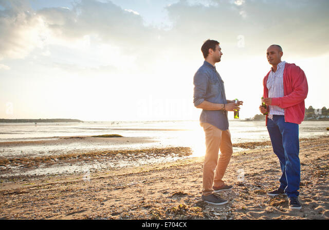 Männer trinken Bier und plaudern am Strand Stockbild