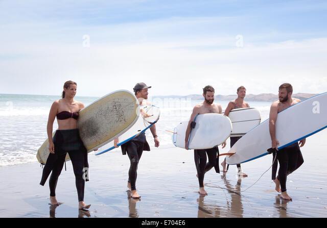 Gruppe von männlichen und weiblichen Surfer-Freunde, die zu Fuß vom Meer entfernt mit Surfbrettern Stockbild
