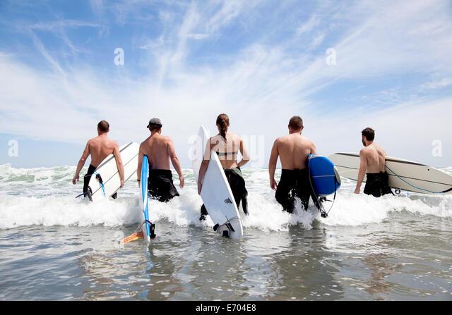 Rückansicht einer Gruppe von männlichen und weiblichen Surfer Freunde waten in Meer mit Surfbrettern Stockbild
