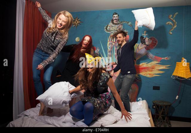 Vier Erwachsene Freunde, die Kissen kämpfen auf Hotelbett Stockbild