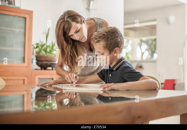 Mutter und Sohn blickte auf Hausaufgaben am Esstisch Stockbild