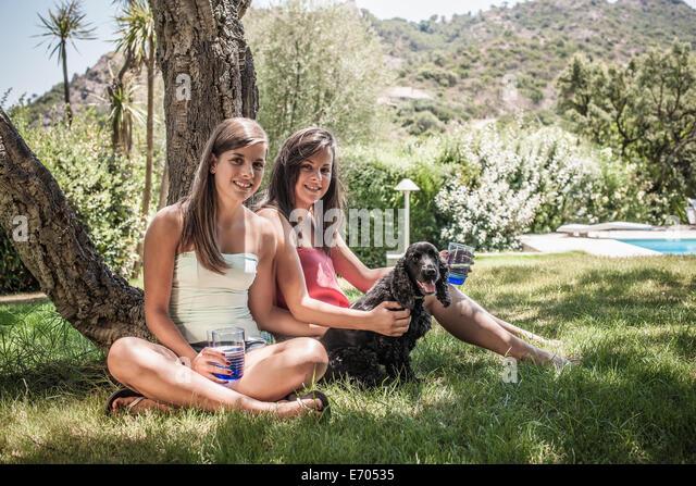 Porträt von zwei Freundinnen mit Hund im Urlaub Hausgarten, Capoterra, Sardinien, Italien Stockbild