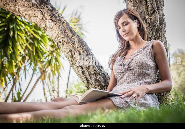 Mitte Erwachsene Frau Buch unter Palme im Urlaub Hausgarten, Capoterra, Sardinien, Italien Stockbild