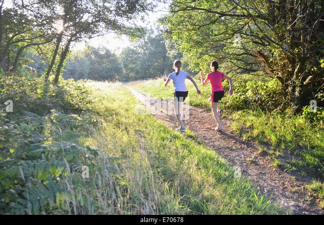 Zwei junge Frauen Läufer läuft bis Wald zu verfolgen, morgen Stockbild