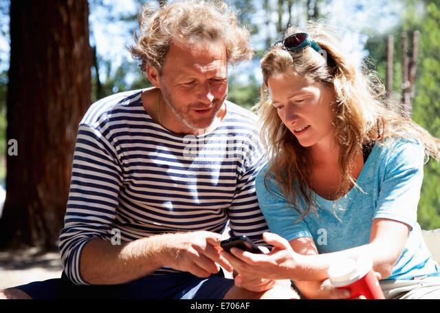 Paar auf der Suche nach unten am Smartphone im Wald Stockbild