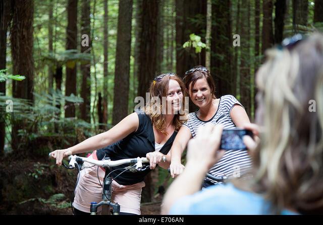 Über Schulter Blick auf Mountainbiker Frauen posieren für Fotos auf Smartphone im Wald Stockbild