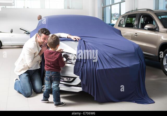 Mitte erwachsenen Mannes aufdecken Neuwagen für Sohn im Autohaus Stockbild