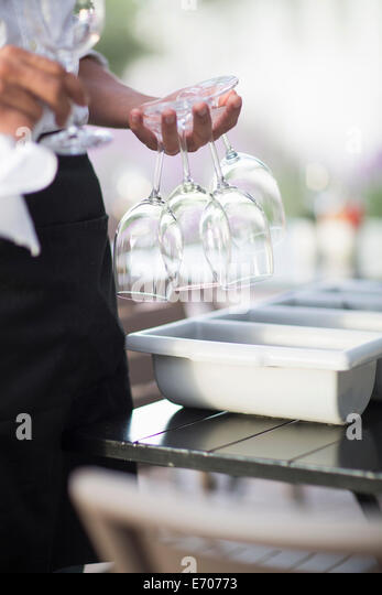 Nahaufnahme von Kellner mit Weingläsern zwischen den Fingern im Restaurant patio Stockbild