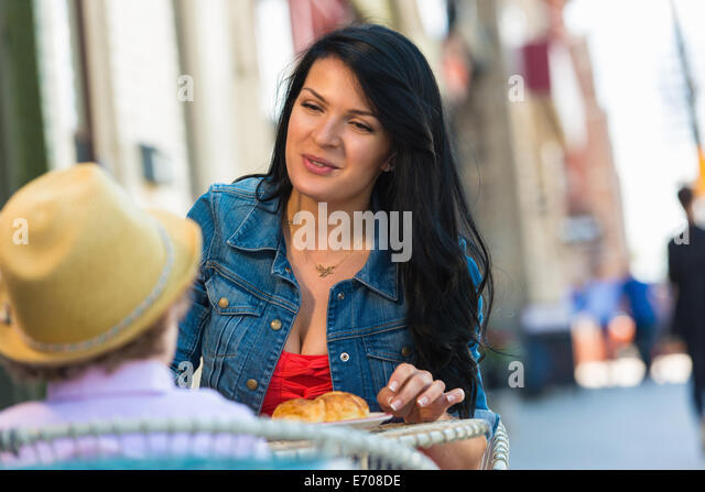 Junge Mutter und Sohn mit Kuchen im Straßencafé Stockbild