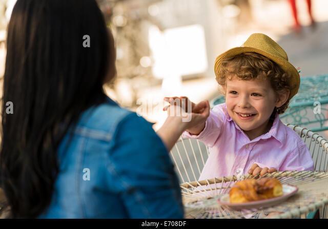 Junge Mutter und Sohn, die Hände berühren, über Tisch im Straßencafé Stockbild