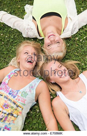 Porträt von drei jungen Freundinnen liegen auf dem Rasen beim Musikfestival Stockbild