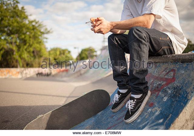 Schuss von jungen männlichen Skateboarder qualmender Zigarette im Stadtpark Skateboard beschnitten Stockbild