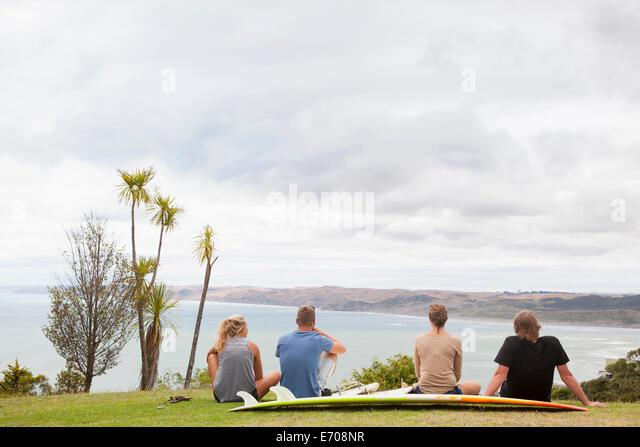 Vier junge Erwachsene Surfer sitzen auf Rasen Weg zum Meer schauen Stockbild