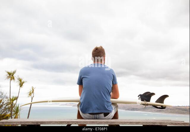 Junge männliche Surfer sitzen auf Picknick Bank wegsehen, Meer Stockbild