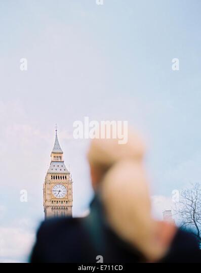 Eine Frau blickte zu Big Ben, The Elizabeth Tower in den Houses of Parliament in London. Stockbild