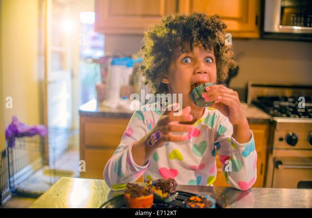 Porträt von überrascht Mädchen essen Muffins am Küchentisch Stockbild