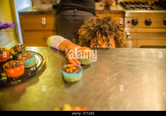 Porträt eines Mädchens für Cupcakes am Küchentisch zu erreichen Stockbild