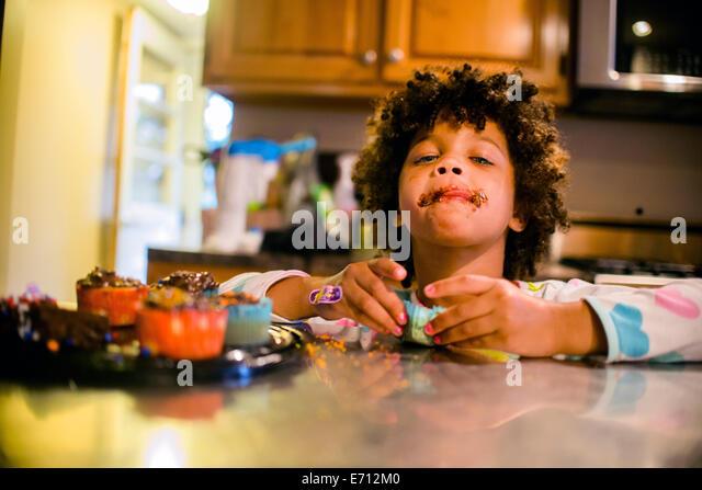 Porträt eines Mädchens mit Schokolade bedeckt Mund Essen Muffins Stockbild