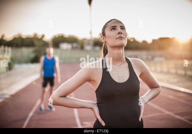 Junge Frau mit Händen auf den Hüften auf Laufband Stockbild