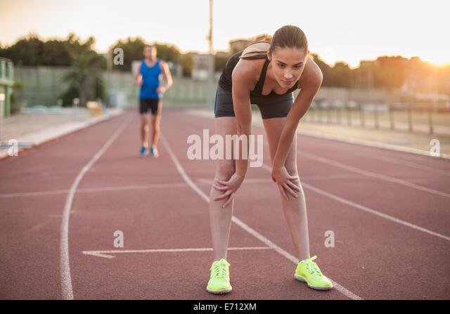 Frau vornübergebeugt auf Rennstrecke Stockbild