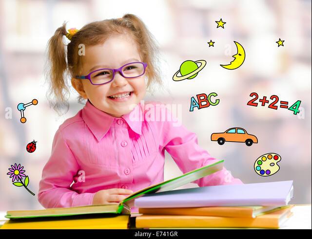 Glückliches Kind Mädchen in Gläsern, die Bücher in der Bibliothek zu lesen Stockbild