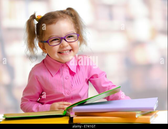 Glückliches Kind Mädchen in Brille lesen von Büchern, die am Tisch sitzen Stockbild