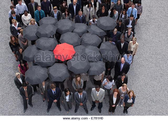 Sonnenschirm am Mittelpunkt des Kreises gebildet von Geschäftsleuten Stockbild