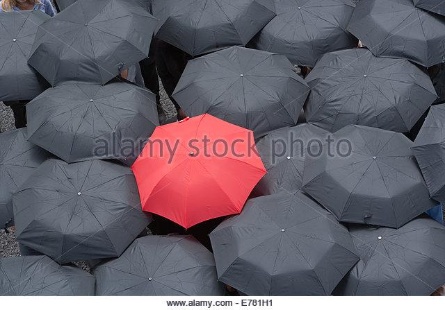 Einem roten Regenschirm im Center von mehreren schwarzen Regenschirmen Stockbild
