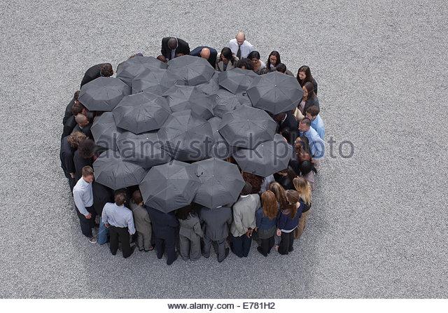 Kreis gebildet von Geschäftsleuten mit Sonnenschirmen Stockbild