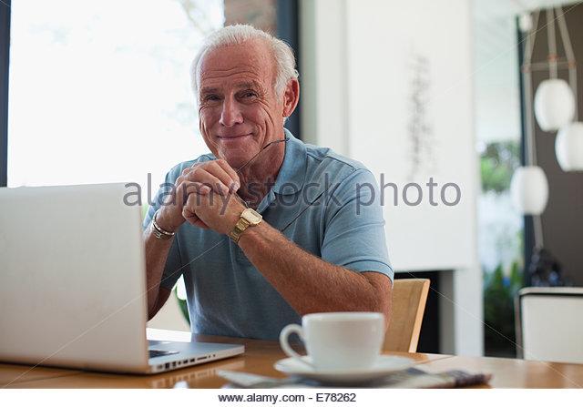 Älterer Mann mit Laptop im Haus Stockbild