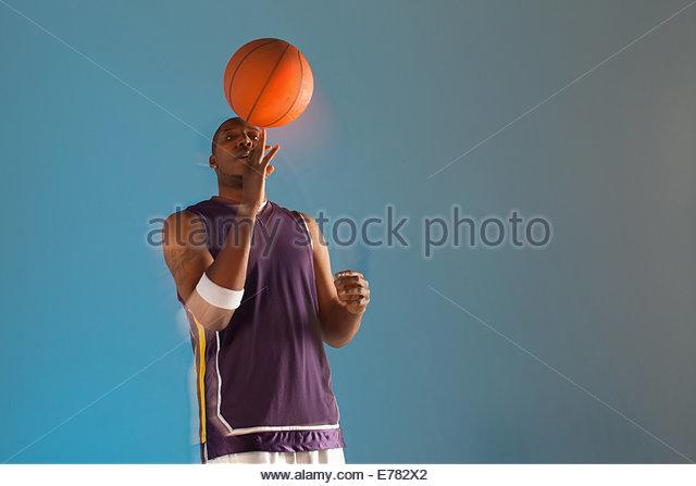 Basketball-Spieler Ball auf einem Finger balancieren Stockbild