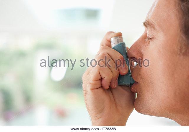 Mann Asthma-Inhalator verwenden Stockbild
