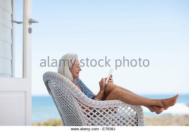 Ältere Frau mit digital-Tablette im Stuhl Stockbild