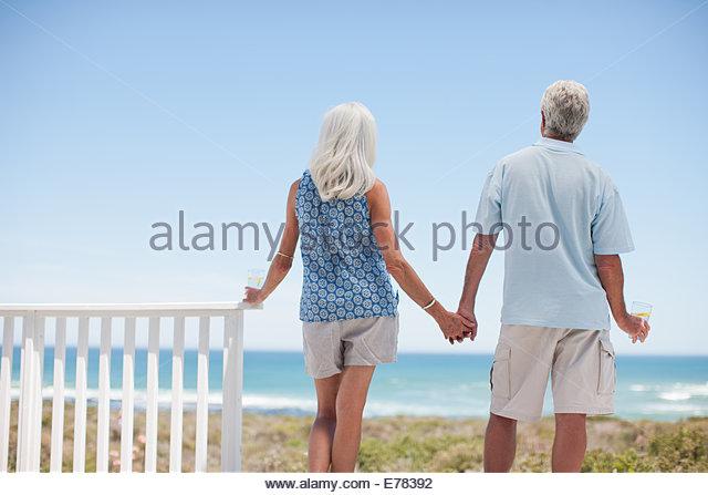 Älteres Paar halten die Hände auf der Strandterrasse Stockbild