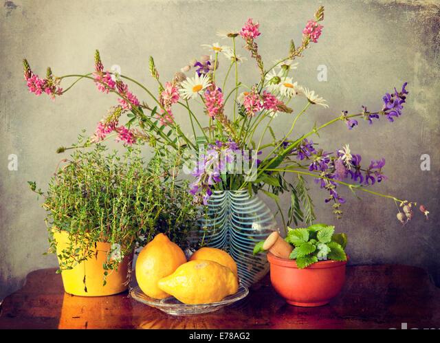 Kräuter aus dem Garten, Wiesenblumen in Vase und Zitrone Obst. Grunge Texturen und Instagram-Retro-Effekt Stockbild